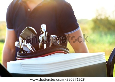 Close up of professional golf gear on the golf course at sunset. Athletic young man playing golf, choising club - stock photo