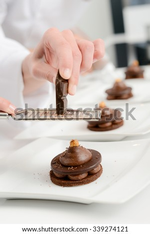 close up of professional pastry cook hands preparing chocolate dessert in restaurant kitchen - stock photo