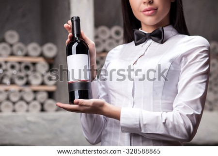 Close up of professional sommelier holding and showing a bottle of red wine. The woman is standing in cellar and smiling - stock photo