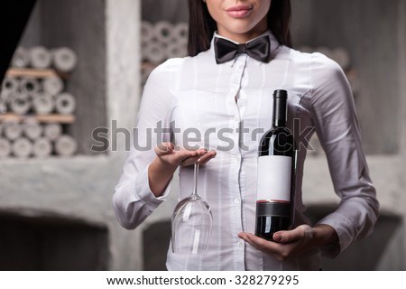 Close up of professional sommelier standing in old cellar. The woman is holding bottle of red wine and glass. She is smiling - stock photo