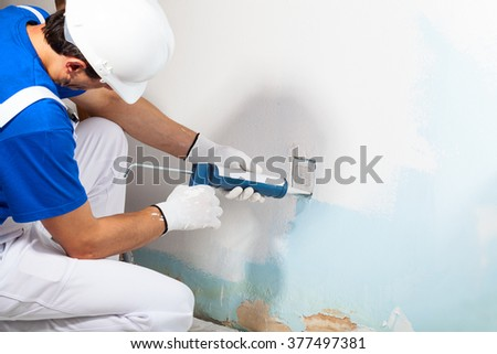 Close-up Of Professional Workman Applying Silicone Sealant With Caulking Gun on the Wall - stock photo