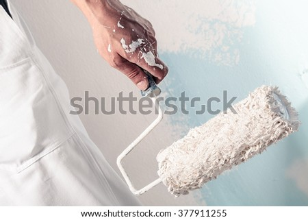 Close up Of Professional Workman Hand holding Dirty Paint roller - stock photo
