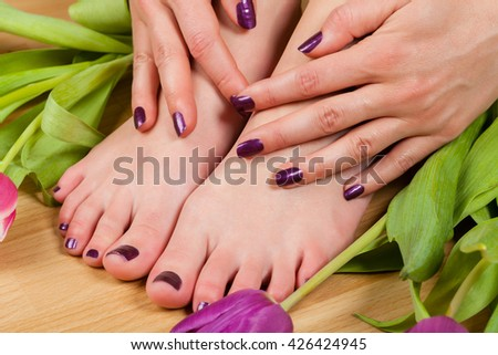 Close up of professionally done pedicure and manicure colored purple by tulips on wood floor - stock photo