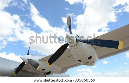 Close up of propellers of airplane flying in blue sky with clouds  - stock photo