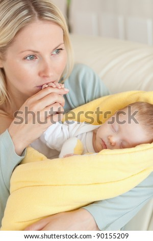 Close up of provident young mother kissing her baby's hand - stock photo