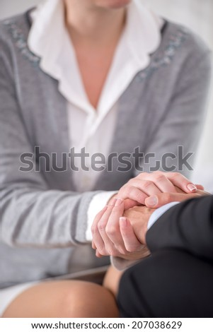 Close-up of psychiatrist keeping her hands together with her patient