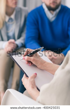Close-up of psychologist writing down notes about young couple on session