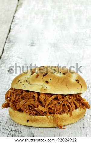 Close up of pulled chicken sandwich on a rustic background. - stock photo
