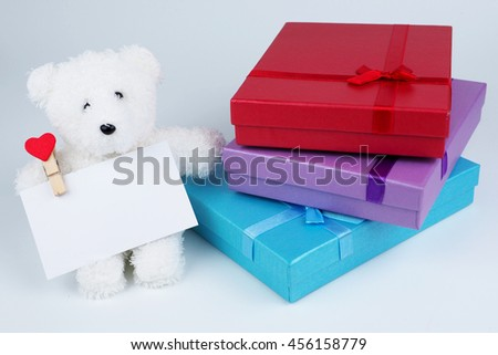 Close up of purple , blue and red giftboxes and white cutty teddy bear holding white card on white background. - stock photo