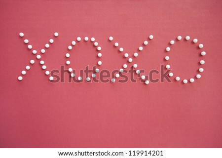 Close-up of push pins in formation of x and o over pink background depicting hugs and kisses