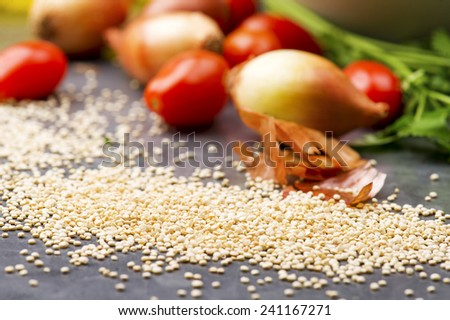 Close up of quinoa grains cherry tomato, onion and parsley - stock photo