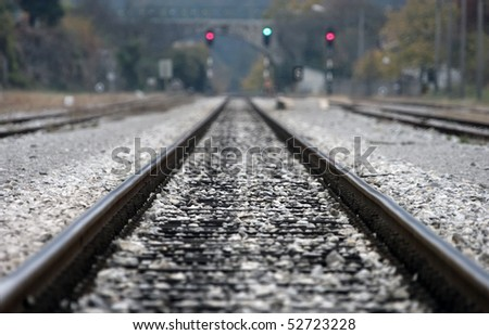 Close up of railway tracks and semafor in the back - stock photo