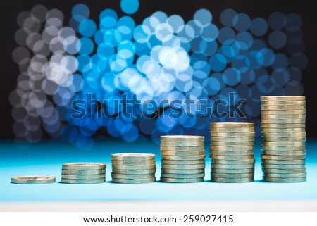 Close-up Of Raising Stack Of Coins With Bokeh Background - stock photo