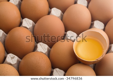 Close up of raw eggs in an egg carton, one broken - stock photo