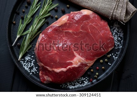 Close-up of raw fresh beefsteak ribeye with seasonings, top view, selective focus - stock photo