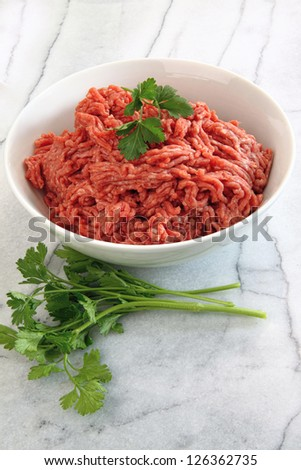 Close up of raw ground beef on marble cutting board - stock photo
