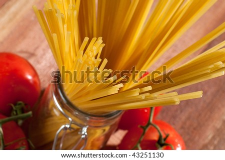 Close up of raw pasta in glass container with fresh tomatoes on the background - stock photo