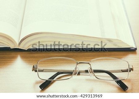 Close up of reading glasses and a book on the desk, vintage style - stock photo