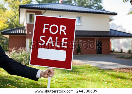 Close-up of real estate agent holding for sale sign - stock photo