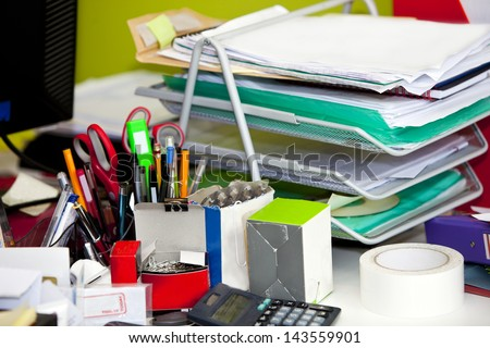 Close-up of real life messy desk in office - stock photo