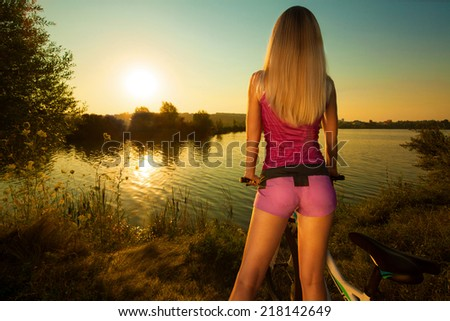 Close-up of rear view of a pretty woman on bicycle relaxing at Sunset. Active Leisure Concept. Healthy lifestyle. - stock photo