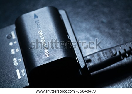 Close up of rechargeable lithium-ion battery with charger - stock photo