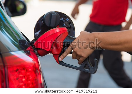 Close up of red fuel nozzle fill enegry of the car. - stock photo