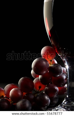 Close-up of red grapes and a glass of red wine - stock photo