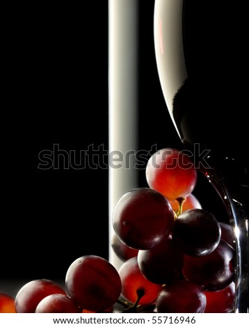 Close-up of red grapes with glass and bottle in background - stock photo