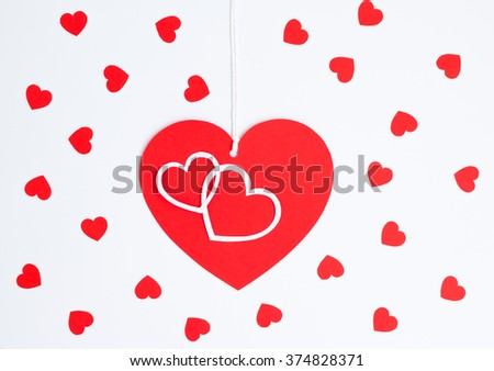 close up of red heart card note with white rope on white background