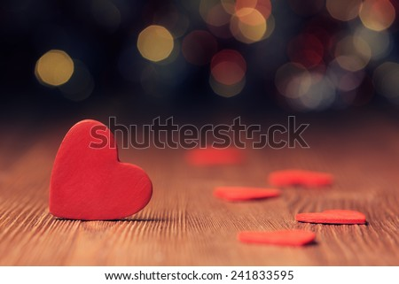 Close up of red heart on old wooden board against defocused lights - stock photo