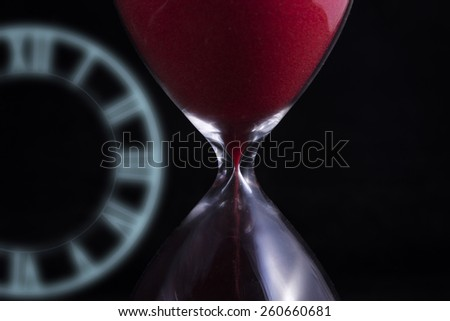 Close up of red hourglass with hologram's clock on black background - stock photo