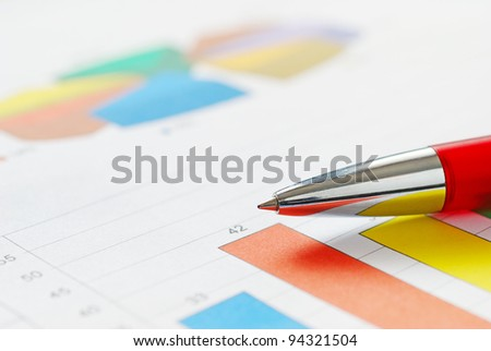 Close-up of red pen and financial graph - stock photo