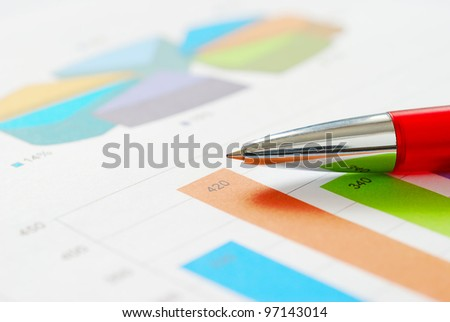 Close-up of red pen of finance report - stock photo