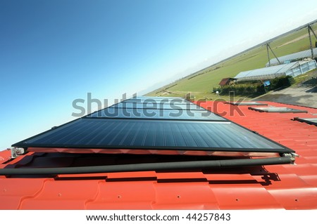 Close up of red roof with solar panel. Blue sky, green field and greenhouse in background. - stock photo