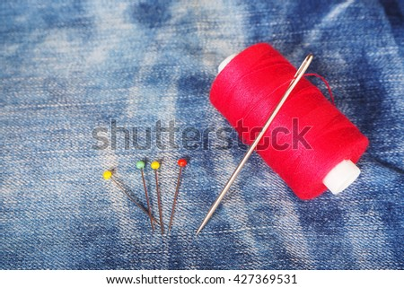 Close up of red sewing thread , yellow sewing pins, green sewing pin, red sewing pin and silver needle on denim, jean background - stock photo
