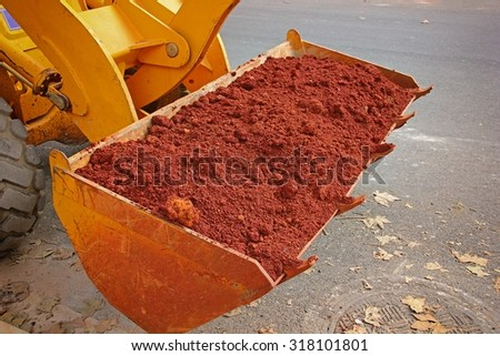 Close-up of red soil in excavator's bucket. - stock photo