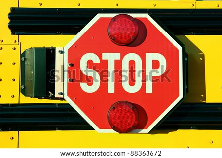 Close up of red stop sign on yellow school bus. - stock photo