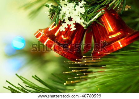 Close-up of red toy bells hanging on green spruce branch decorated with paper snowflake - stock photo