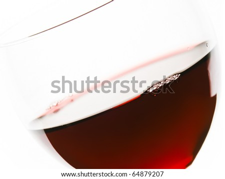 Close-up of red wine and glass focus on the rim. - stock photo