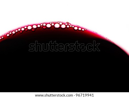 Close-up of red wine bubbles in a transparent glass - stock photo
