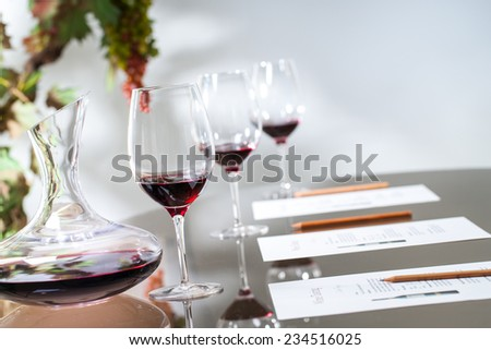 Close up of red wine decanter with glasses on table. - stock photo