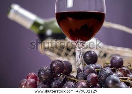 Close-up of red wine glass surrounded by grapes, in front of Rioja wine bottle