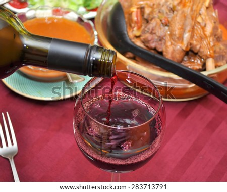 Close up of red wine pouring into a wine glass. Different food is on the table in the blurred background.