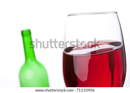 Close-up of red wine wineglass and empty bottle on background