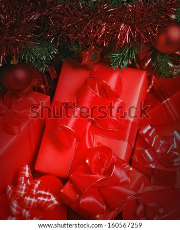 close up of red wrapped parcels with a ribbons under christmas tree - stock photo