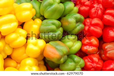 close up of red, yellow and green peppers on market stand - stock photo