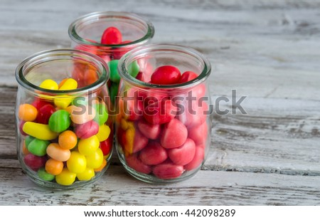 Close-up of red,yellow and pink candies in glass jars on wooden table - stock photo