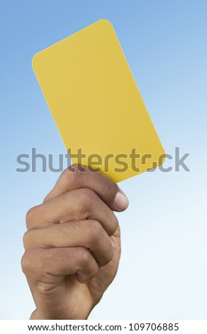 Close-up of referee's hand holding a yellow card that indicates a warning to a player for a foul - stock photo