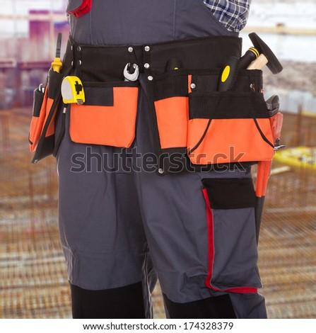 Close-up Of Repairman With Tool In Orange Tool Bag - stock photo